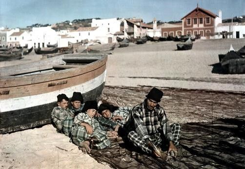 W. Robert Moore. Four men rest beside a fishing boat while one man mends a net. Nazare, Leiria, Portugal. 1930s.