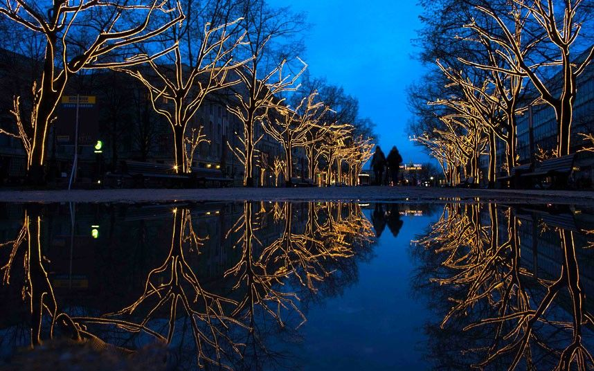 Trees decorated with Christmas lights are reflected in a puddle as people walk along the Unter den Linden boulevard in Berlin