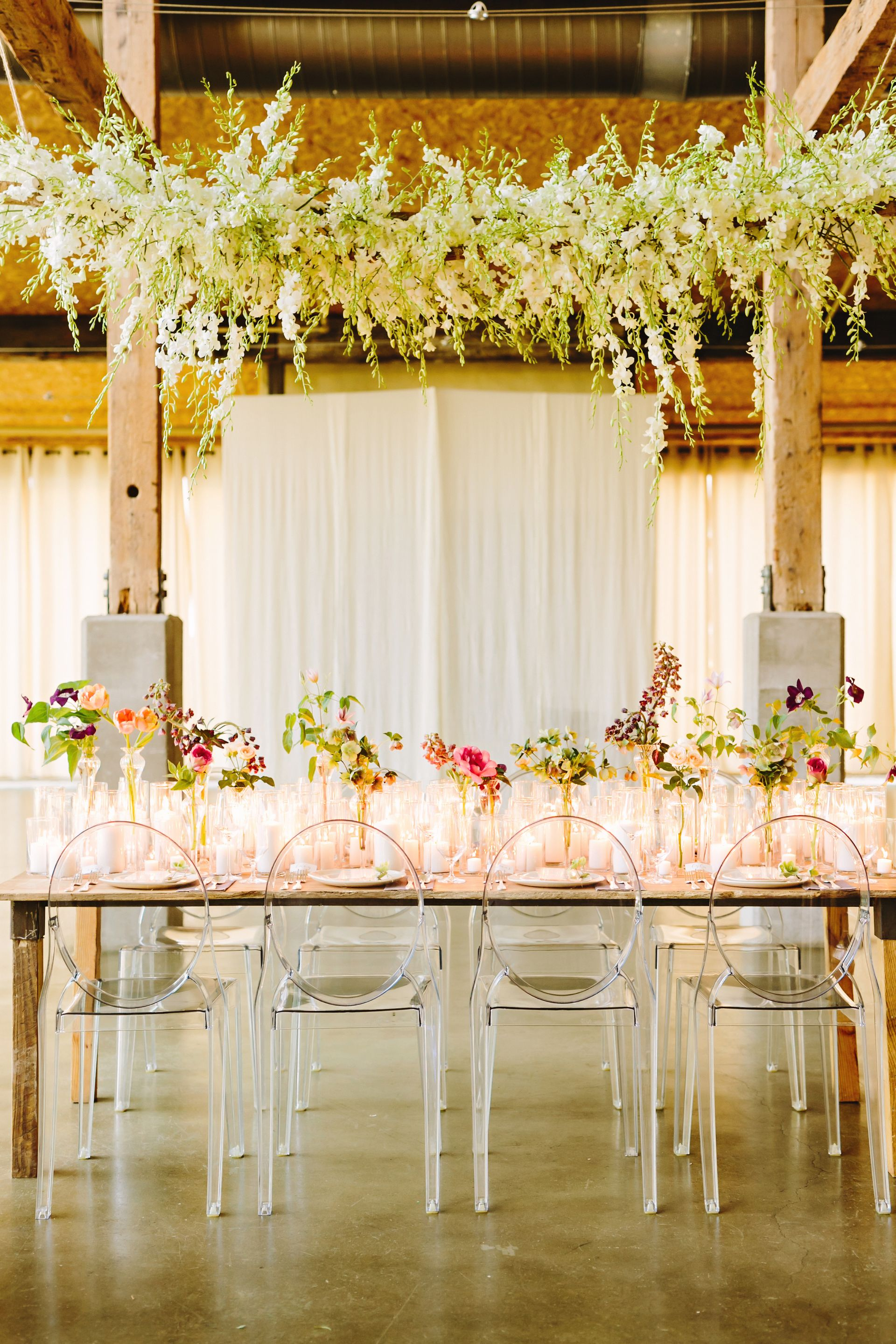 Lucite chairs, romantic reception, white candles galore, vases of pink florals, hanging white floral arrangement from the ceiling // Julie Wilhite Photography