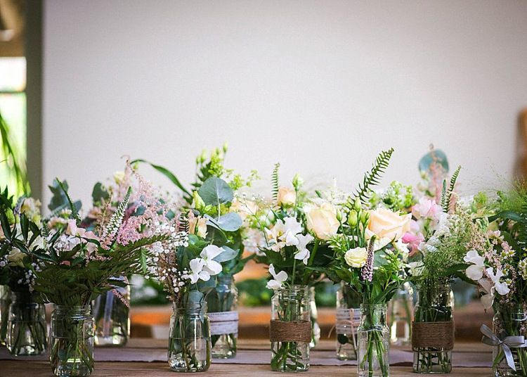 Handmade floral displays in jam jars using pastel coloured wild flowers | Photography by http://www.julieanneimages.com/