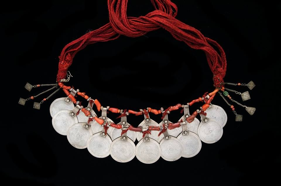 "Large and imposing necklace (""tazelagt"") of a double row of silver discs engraved with nielloed spirals, separated by branch coral and tiny shells and attached to colourful cords. South-west Morocco, Sous Valley. Published in Truus Daalder, *Ethnic Jewellery and Adornment*, p. 406. Truus and Joost Daalder collection; ex collection Mia van Bussel, Amsterdam."