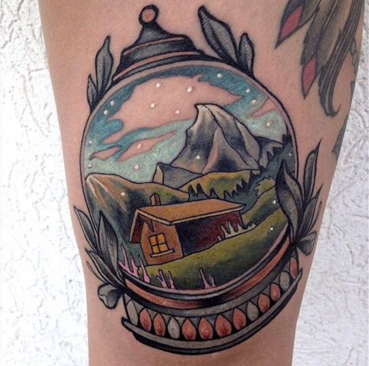 There is incredible clarity in this snow globe tattoo depicting a classic mountain scene.