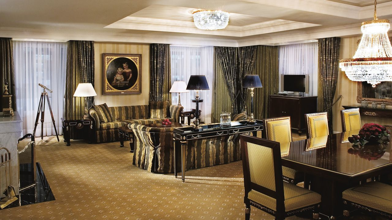 A spacious living room with fireplace, dining table for 10 and a full entertainment center allow guests of The Ritz-Carlton Suite to host friends and family. The Ritz Carlton Hotel, Berlin