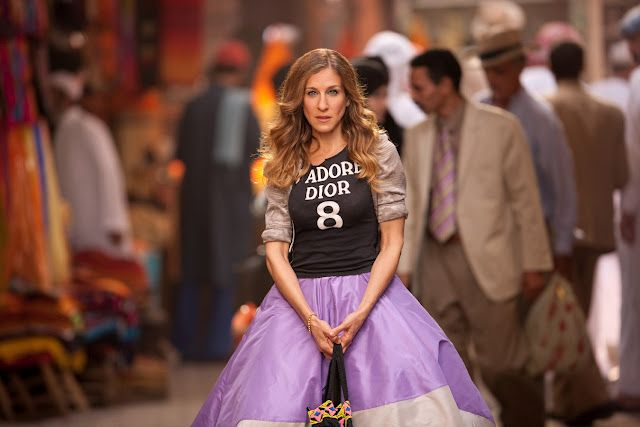 Carrie Bradshaw in trademark full skirt paired with a 'J'adore Dior' t-shirt.