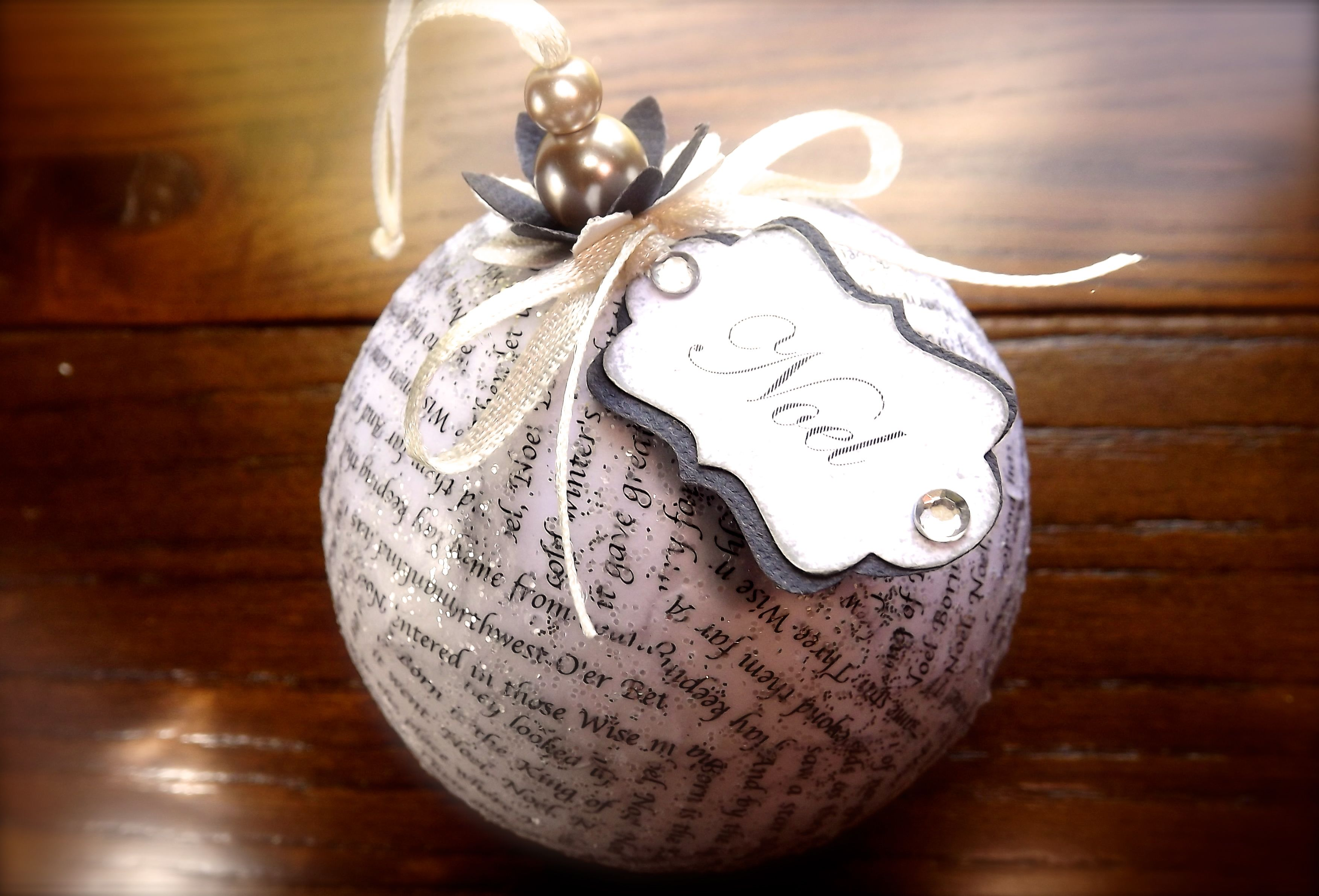 """Christmas decoration ornament featuring decoupaged Christmas carol lyrics, shimmering with a splash of glitter and tags printed with the key word of the song - """"the first noel"""", """"Joy to the world"""" and """"Jingle bells""""."""