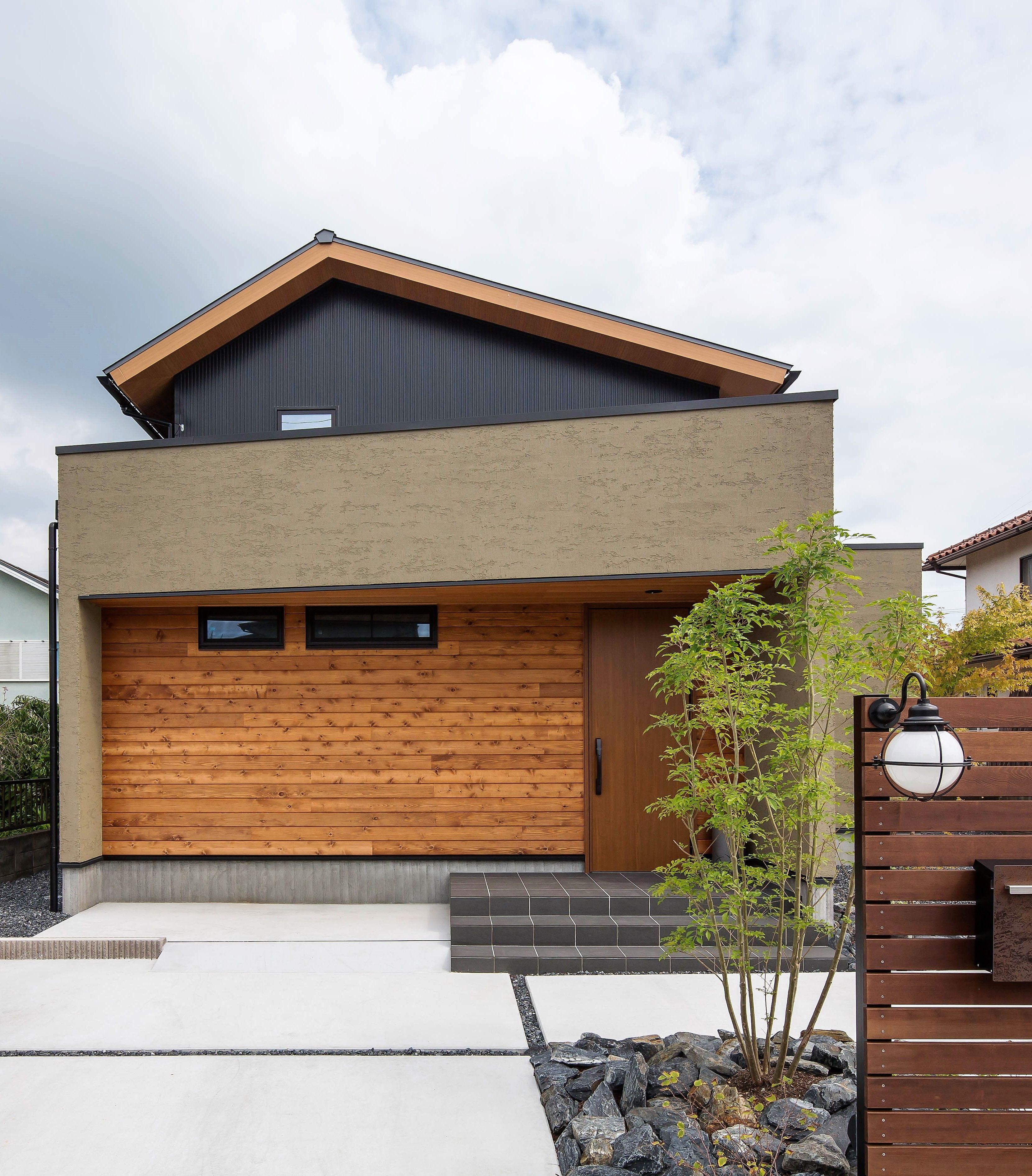 アシンメトリックな屋根形と斜めに切り取られたポーチが 住宅街の中で