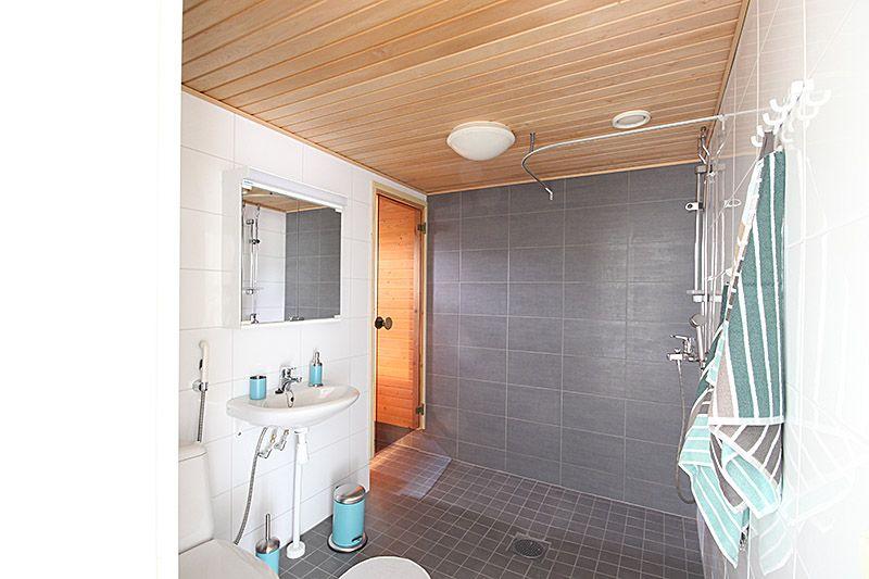 Turkoosilla viimeistelty harmaa-valkoinen kylpyhuone Helsingissä