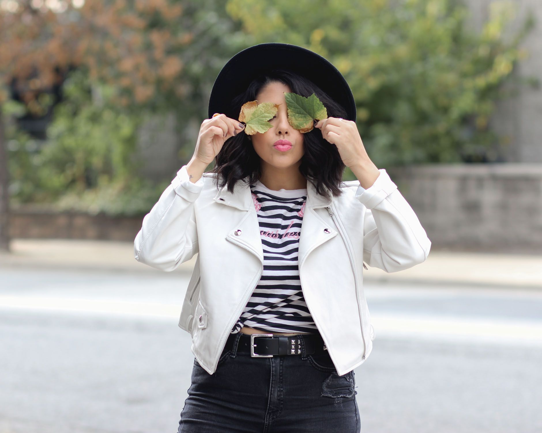 23f6073a332 lifestyle blogger naty michele wearing a white faux leather jacket and  holding leaves