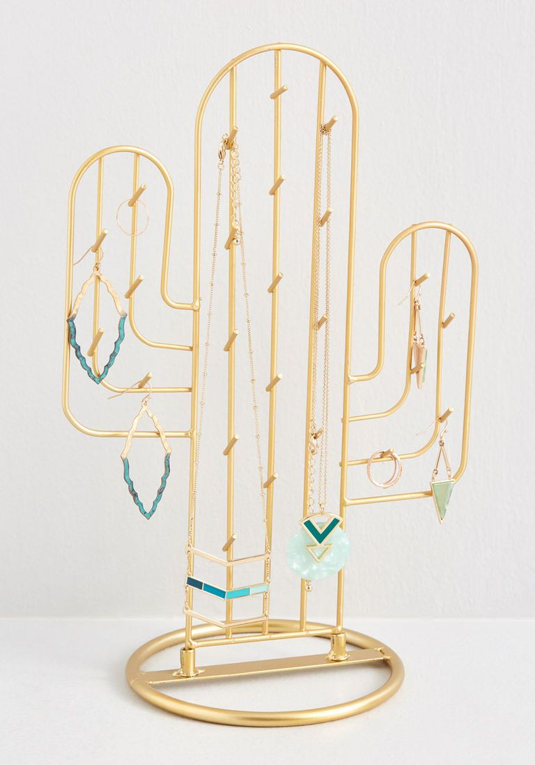 Saguaro Storage Cactus Jewelry Stand is part of Jewelry stand, Cactus jewelry, Cute jewelry, Jewelry rack, Unique jewelry, Jewelry organization - Saguaro Storage Cactus Jewelry Stand  This gold metal cactus won't just decorate your dresser top delightfully  it'll boost its functionality, as well! Replete with upwardtilted spikes that welcome your earrings, necklaces, and bracelets to hang out until the next time they're chosen to be worn, this stylish jewelry stand will be anything but deserted