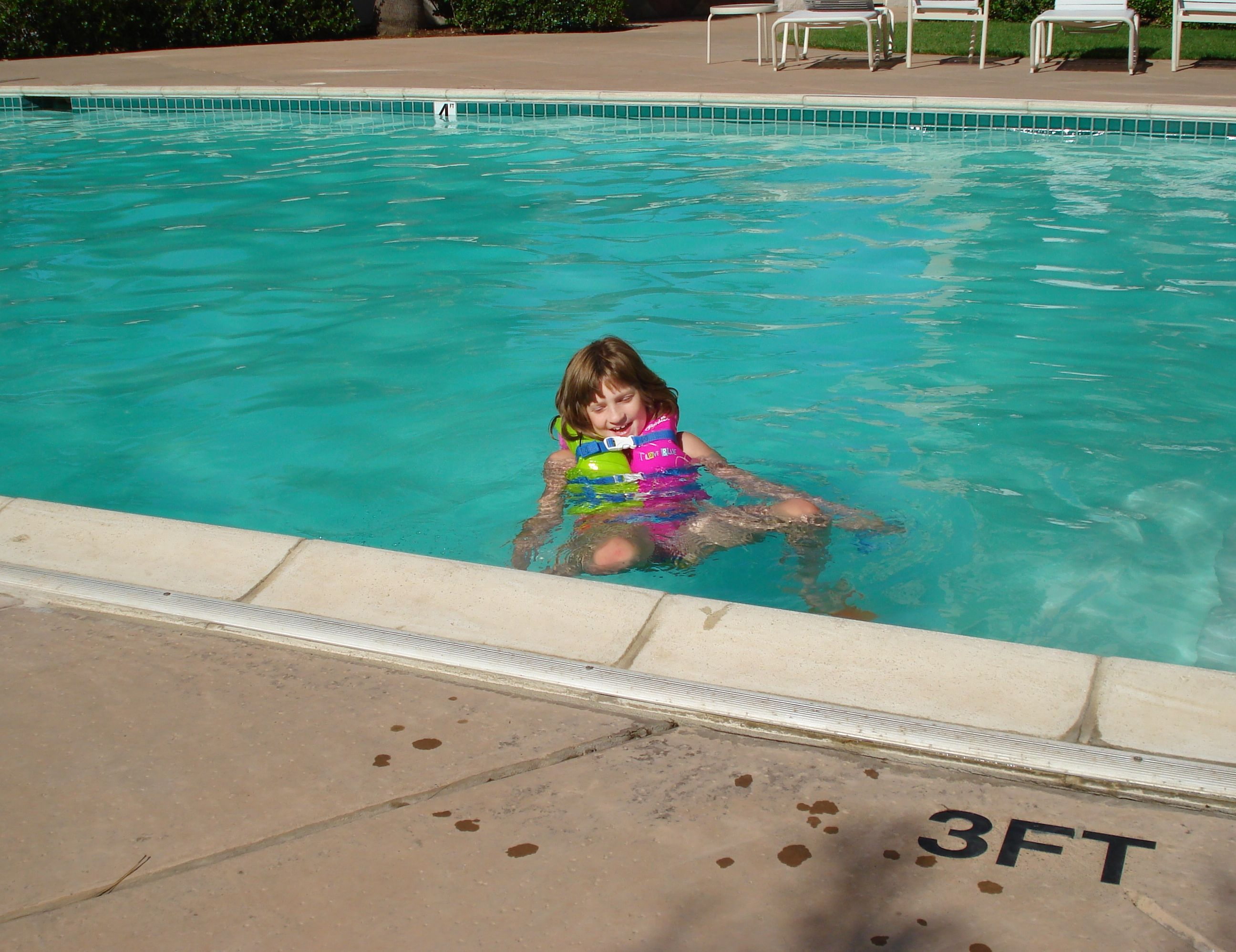 tall kid swims in big hotel pool