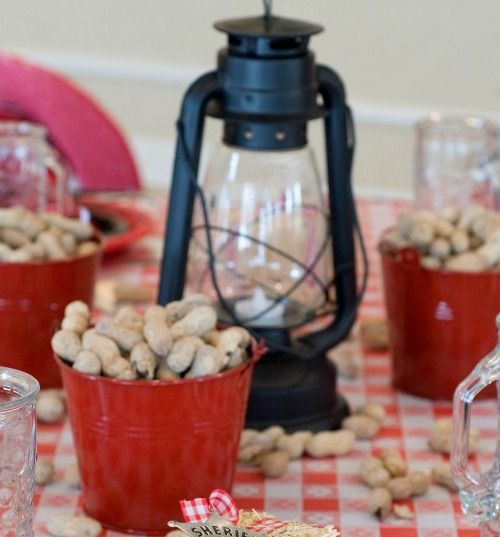 place tin buckets on the table and fill them with peanuts pretzels or other snacks as for the centerpiece use mini hay bales and western lantern