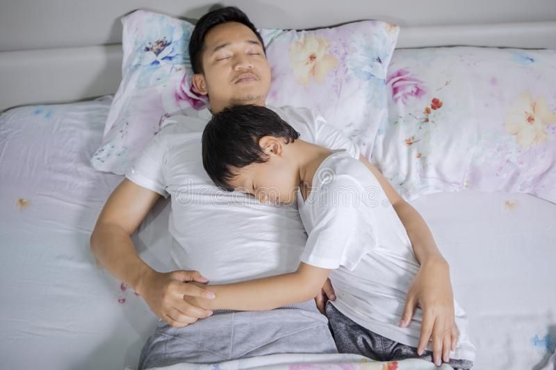Boy and his father sleeping peacefully on bed stock image