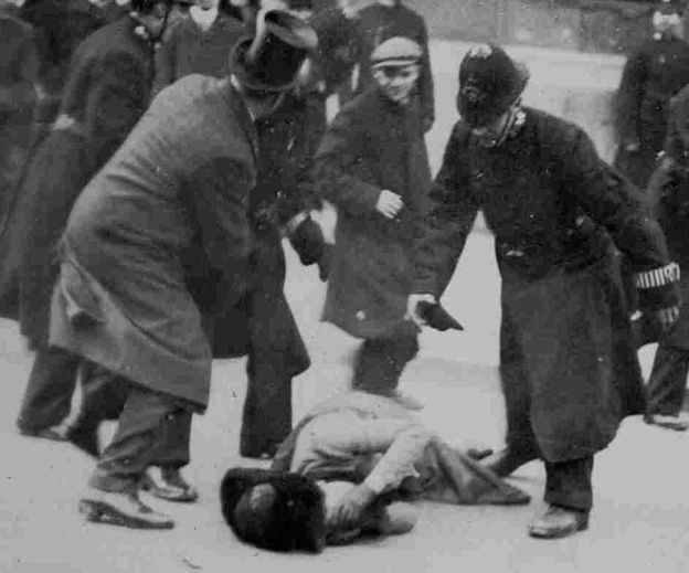 Woman lying on ground after being injured, surrounded by policemen, 18 November 1910. She was attacked, by police and the men around her, for campaigning for the vote for women.