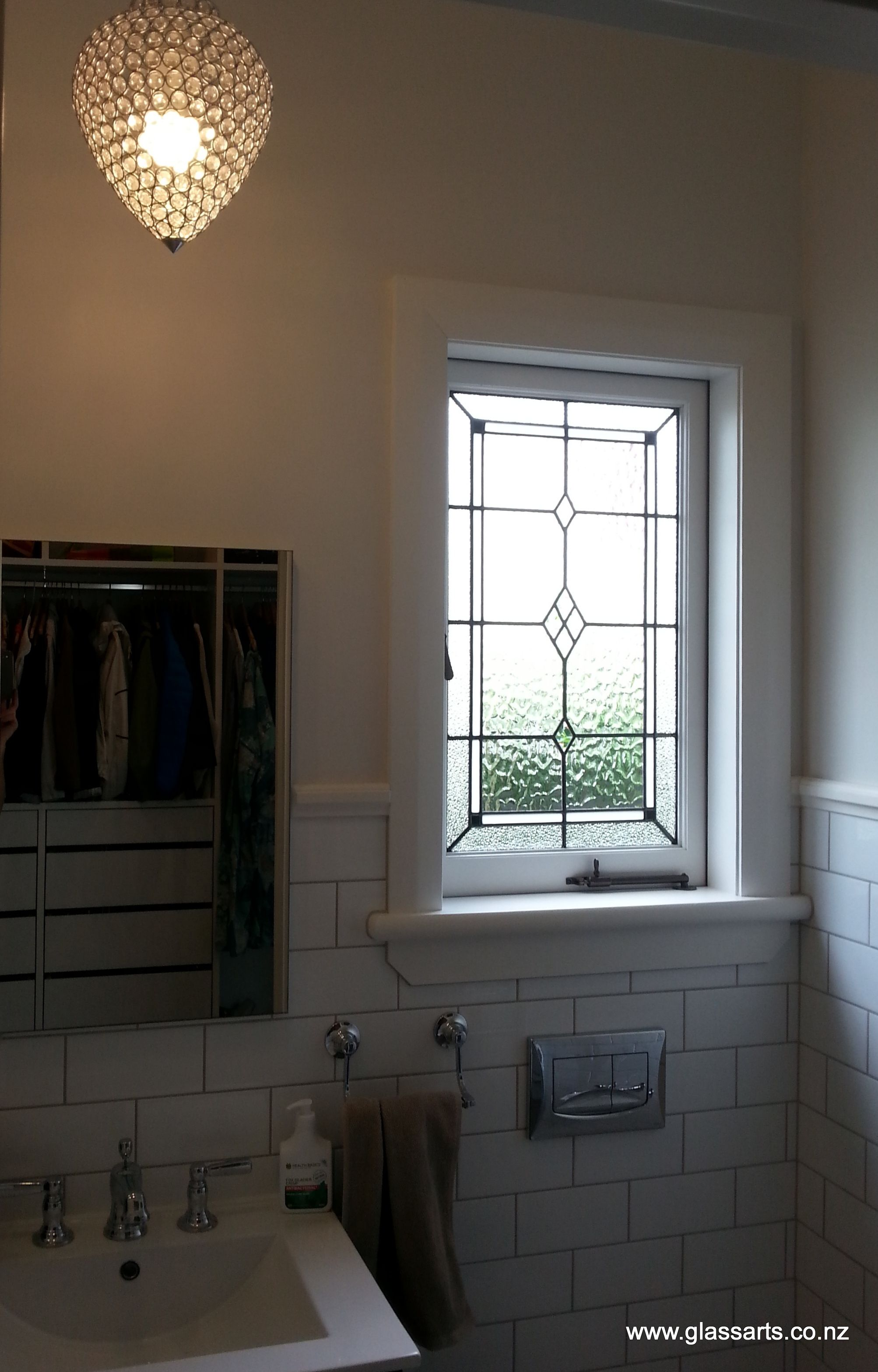 Custom stained glass window adding character to bathroom
