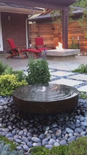 Modern Backyard Stone Water Feature And Concrete Fire Pit The Small River Rock Surround Makes This