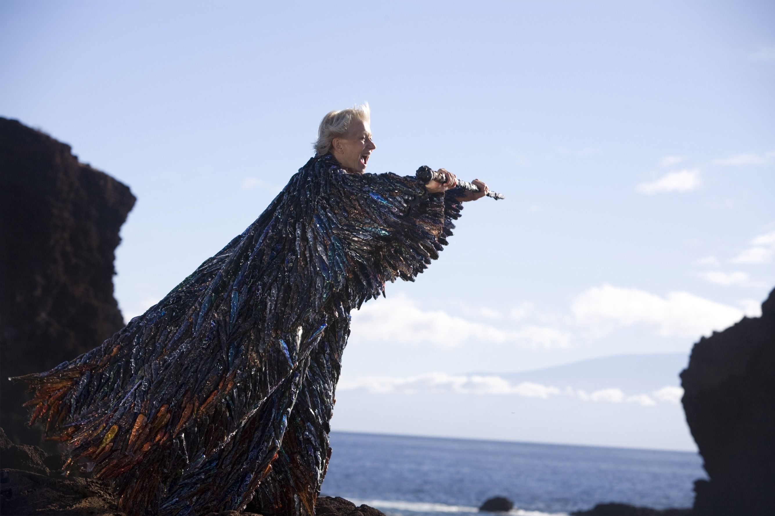 Helen Mirren as Prospera in The Tempest (2010). Prospera the sorceress is standing on a cliff in front of the ocean under a blue sky. She has short white hair and is wearing an enormous cloak which trails to the floor, make up of hundres of pieces of a shiny material in an array of dark colours. She is holding a staff horizontally in front of her, mouth open in a shout.