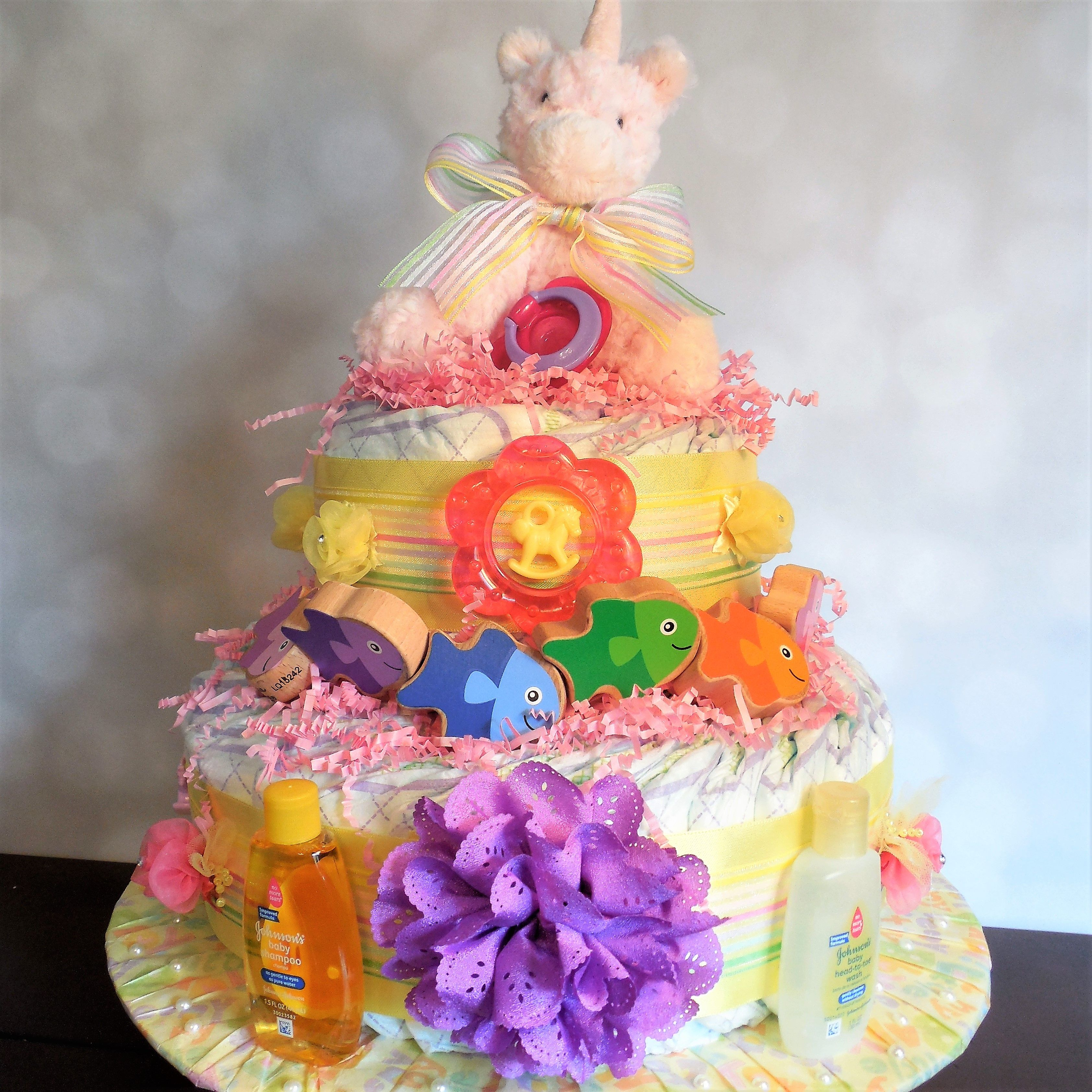 Rainbow & unicorn themed diaper cake with teethers wooden toys
