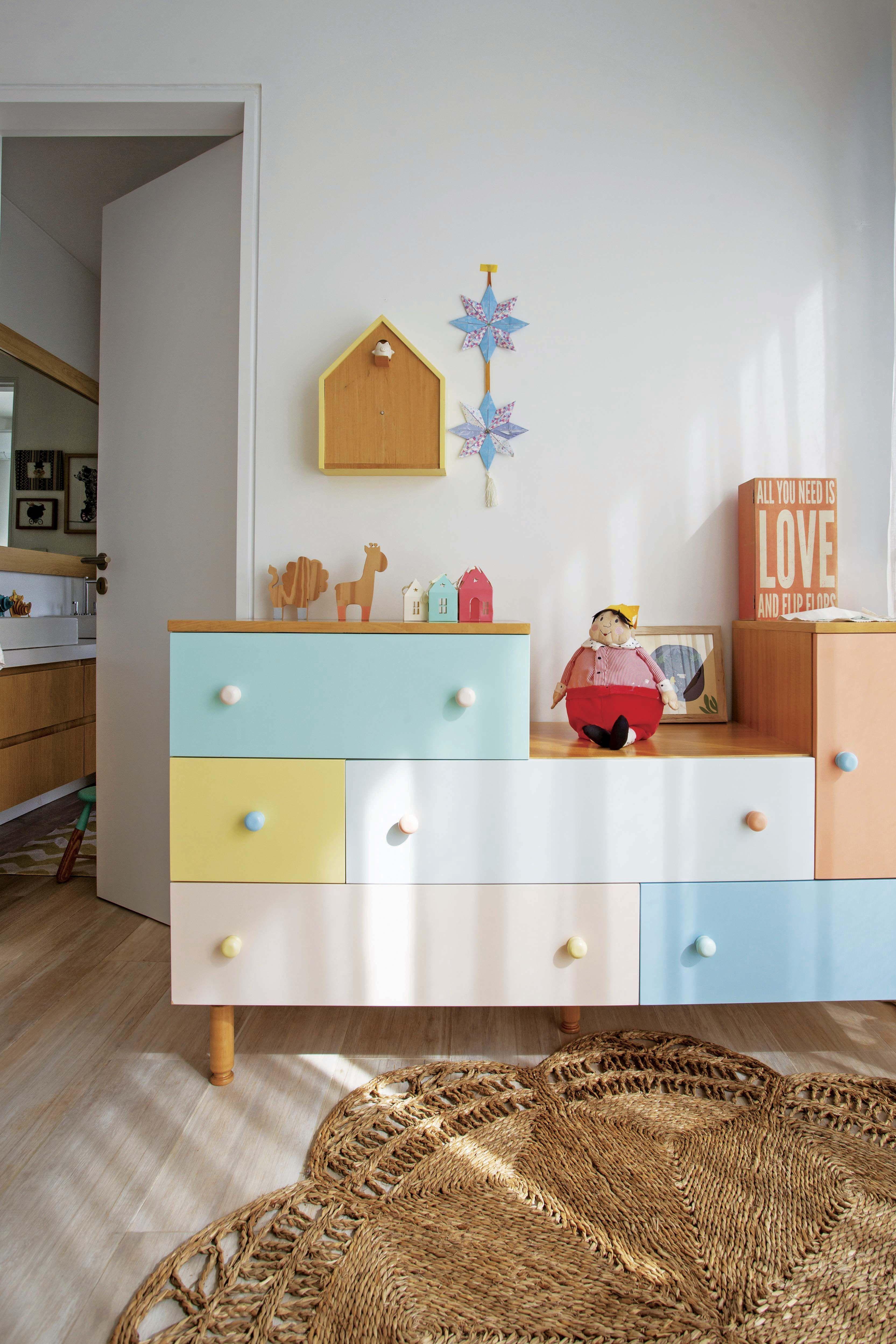 En una casa cuarto de una nena conectado con un baño con cómoda de colores y alfombra circular de yute