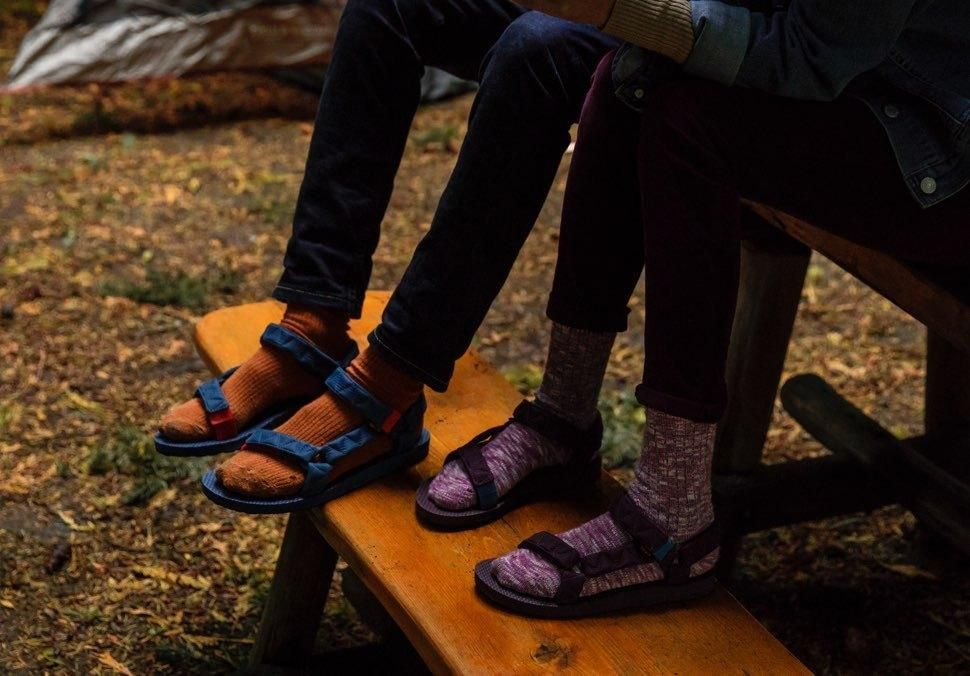 f2cede24c Two people sitting on picnic table wearing socks and Teva Universal Puff  sandals.