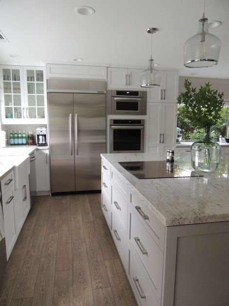 Exceptionnel White Kitchen With Light Wood Floors And Solid Stainless Appliances.