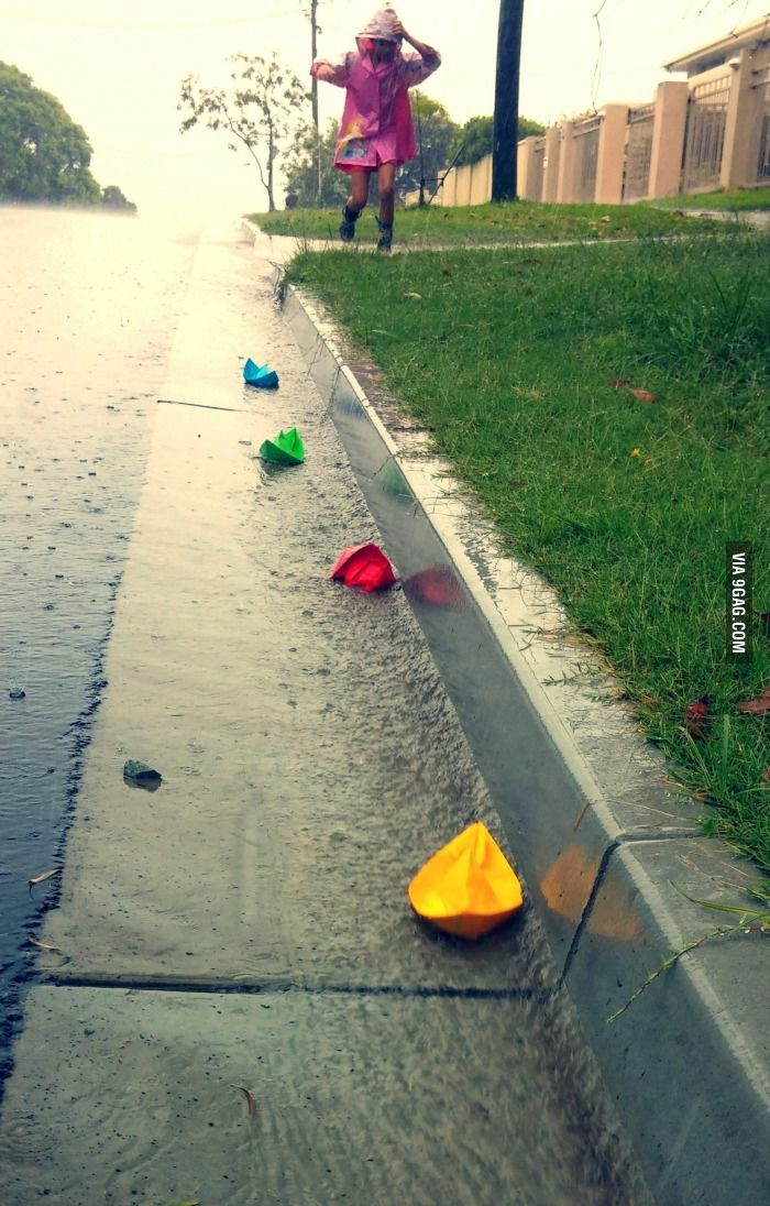 This little girl is chasing paper boats in the rain.