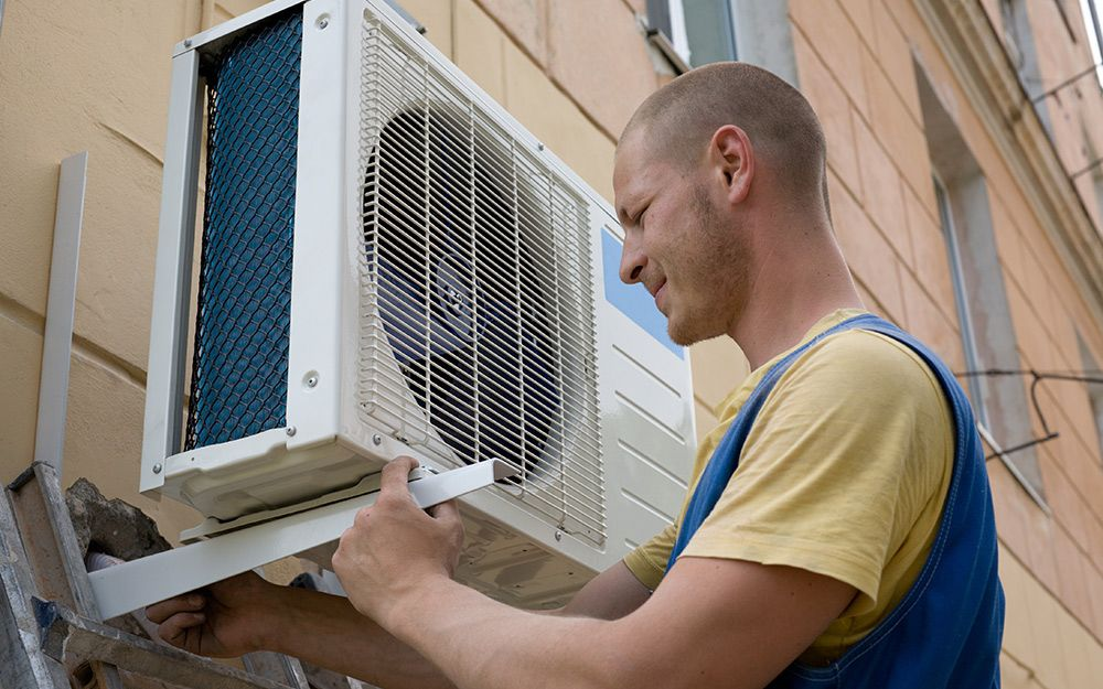 A man installing the outdoor unit of a mini split air