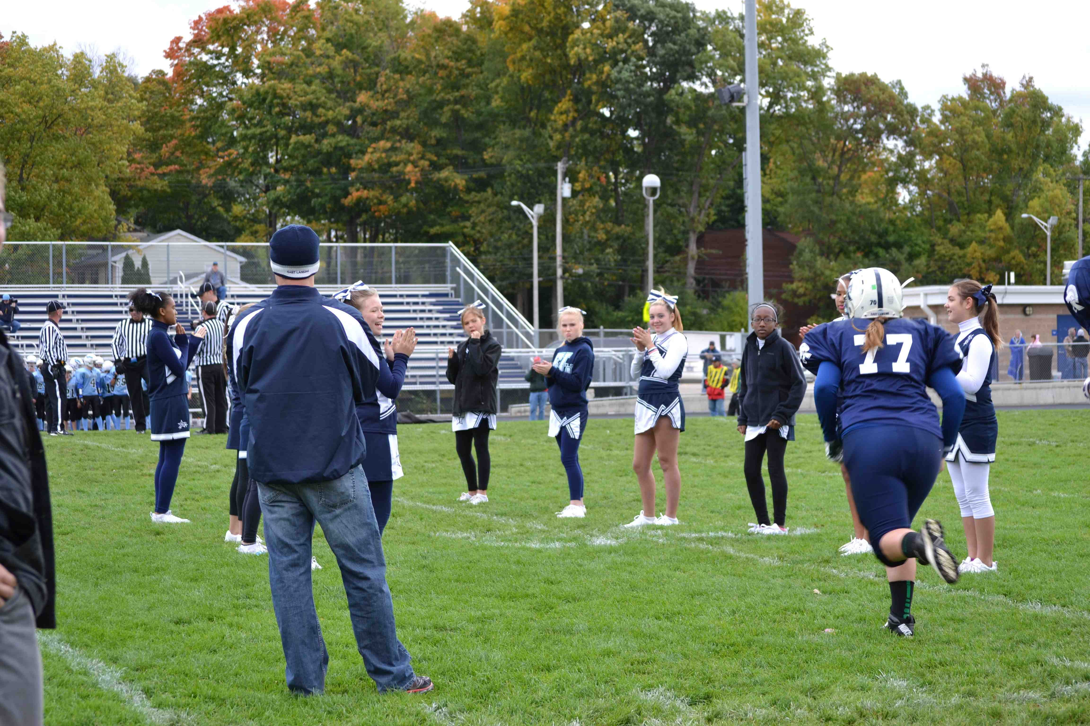 Eva runs onto the field as her name is called. Many of the cheerleaders are her friends.