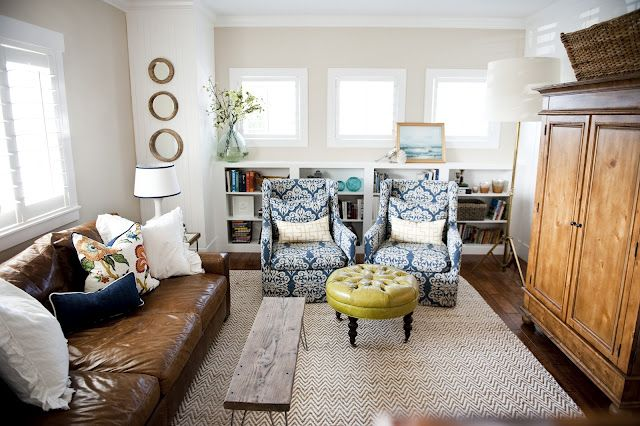 Easy living space. The ingredients: neutral walls, handsome leather couch and a great rug. We love that personality was thrown in with the printed chairs and bold-colored ottoman.