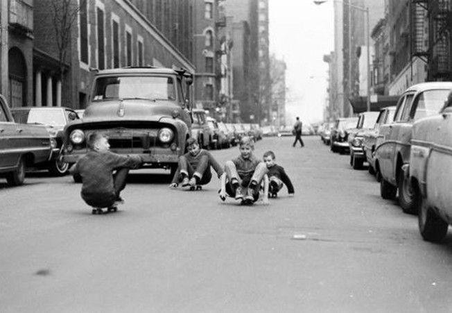 Kids cruising down the street 1960