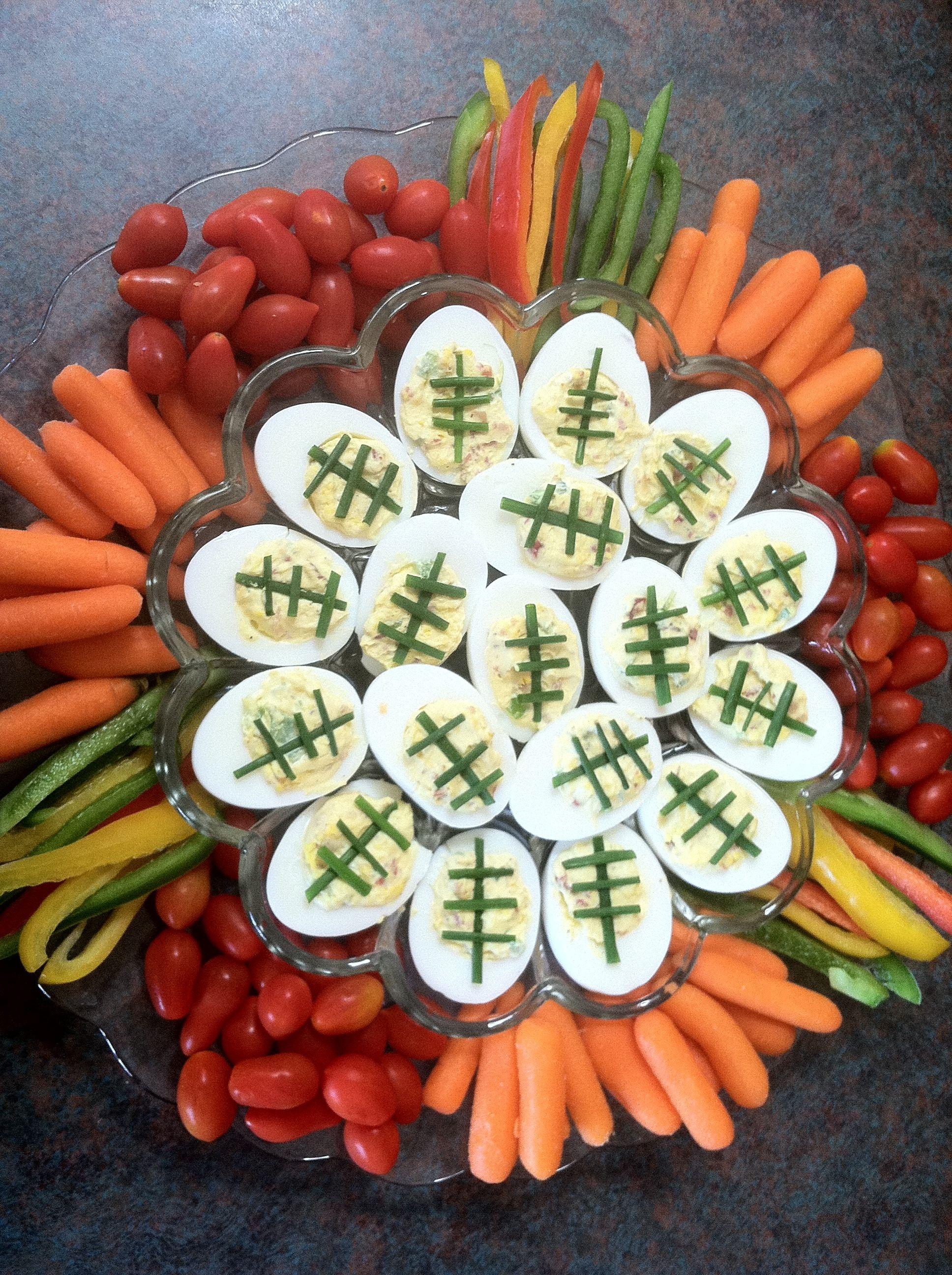 Footballthemed deviled eggs featured on a veggie plate