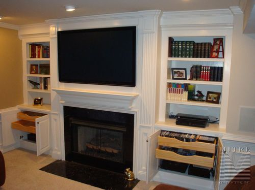 Custom Mantel Surround With Fluted Paneled Pilasters Recessed Built In Cabinetry Base Cabinet Storage Pull Out DVD Trays