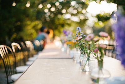 Camino de mesa con pequeños jarrones y flores de colores. Boda hipster al aire libre organizada por Detallerie. Table runner with little vases filled with colorful flowers. Outdoors hipster wedding by Detallerie.