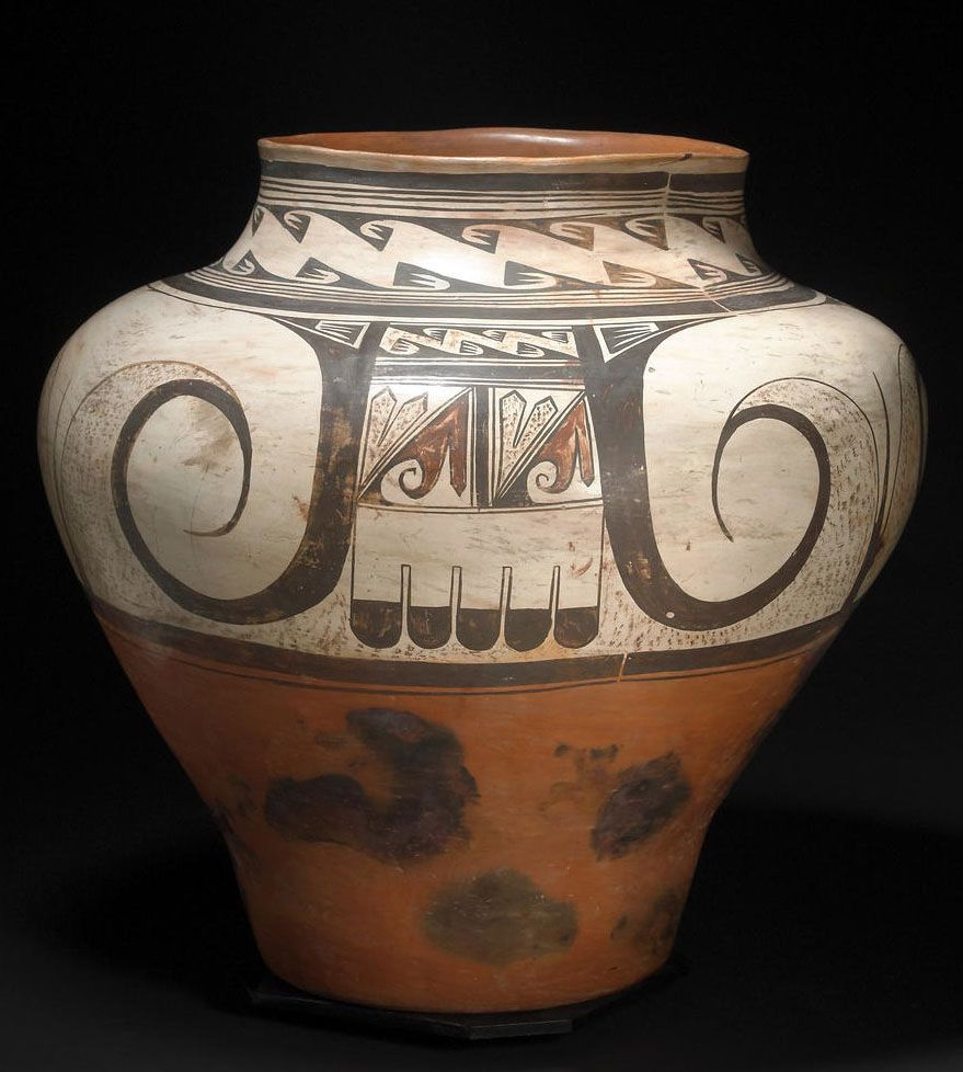 Hopi polychrome storage jar | Nampeyo, decorated with three images of the eagle tail composition, marked by broad spirals and geometric complements, a neck band of repeated hooked wing motifs between multiple banding lines, an area of repair with minor restoration to the rim.