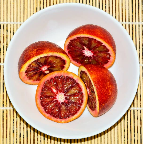 sliced red oranges in white plate closeup