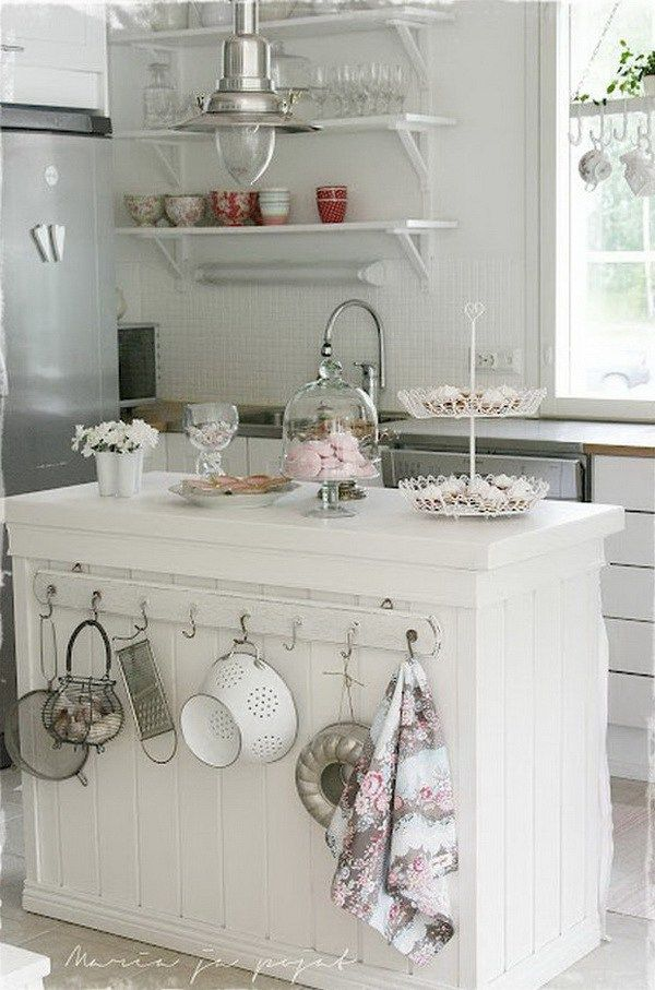White shabby chic kitchen island with slightly mismatched hooks on one side on my pastry prep block