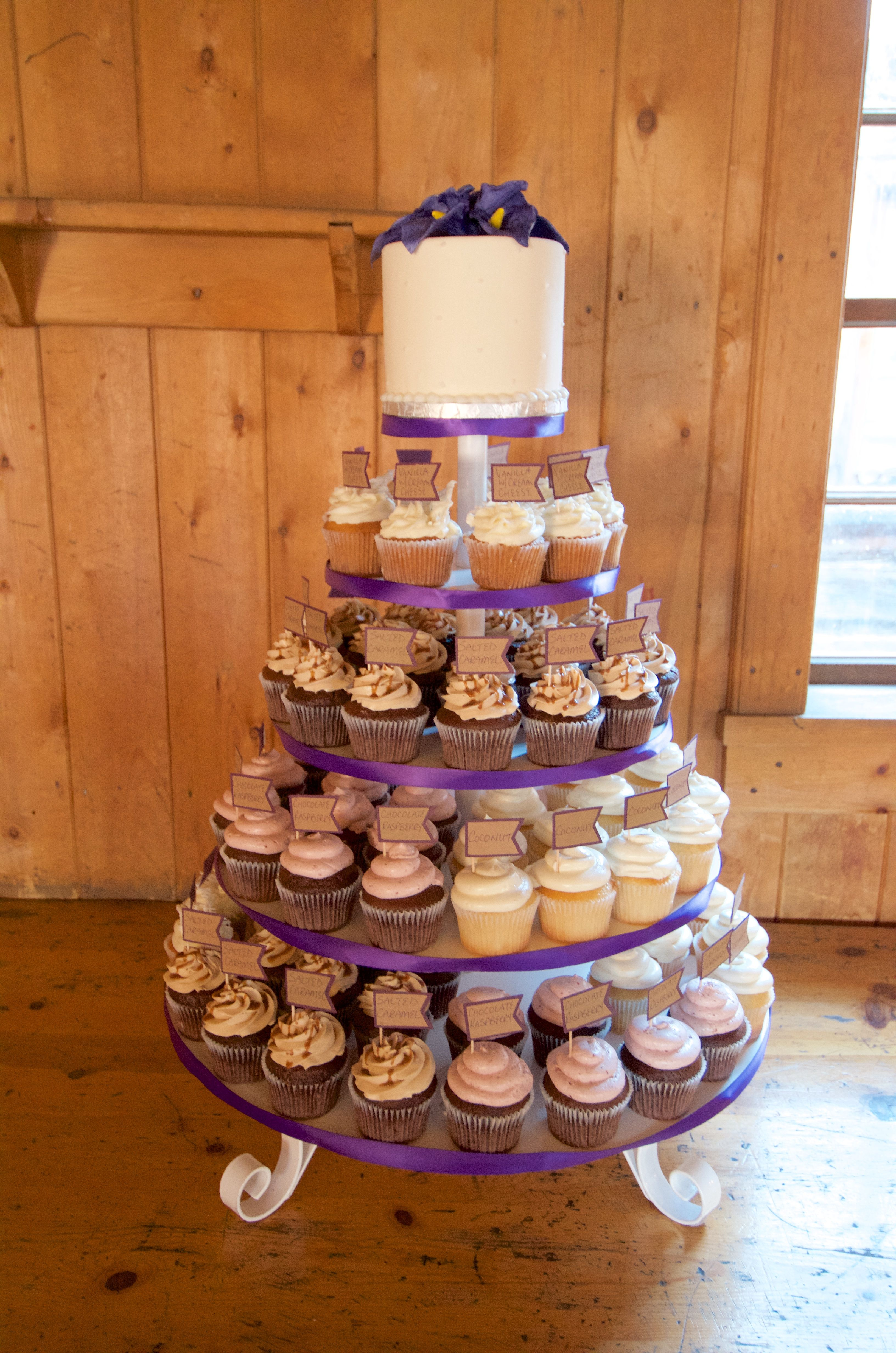 Plane Jane Buttercream Cake Topper With Purple Ribbon On A Wedding Cupcake Stand