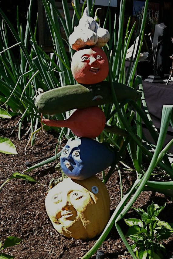 <3 Veggie garden totems are made of high fired clay.  Each vegetable (tomato, garlic, squash, eggplant, beet, corn, pumpkin, or cauliflower) is handmade and most have a face on either side for viewing from any angle.  Designed to welcome friends to your veggie garden, they can also be put in a kitchen for the winter