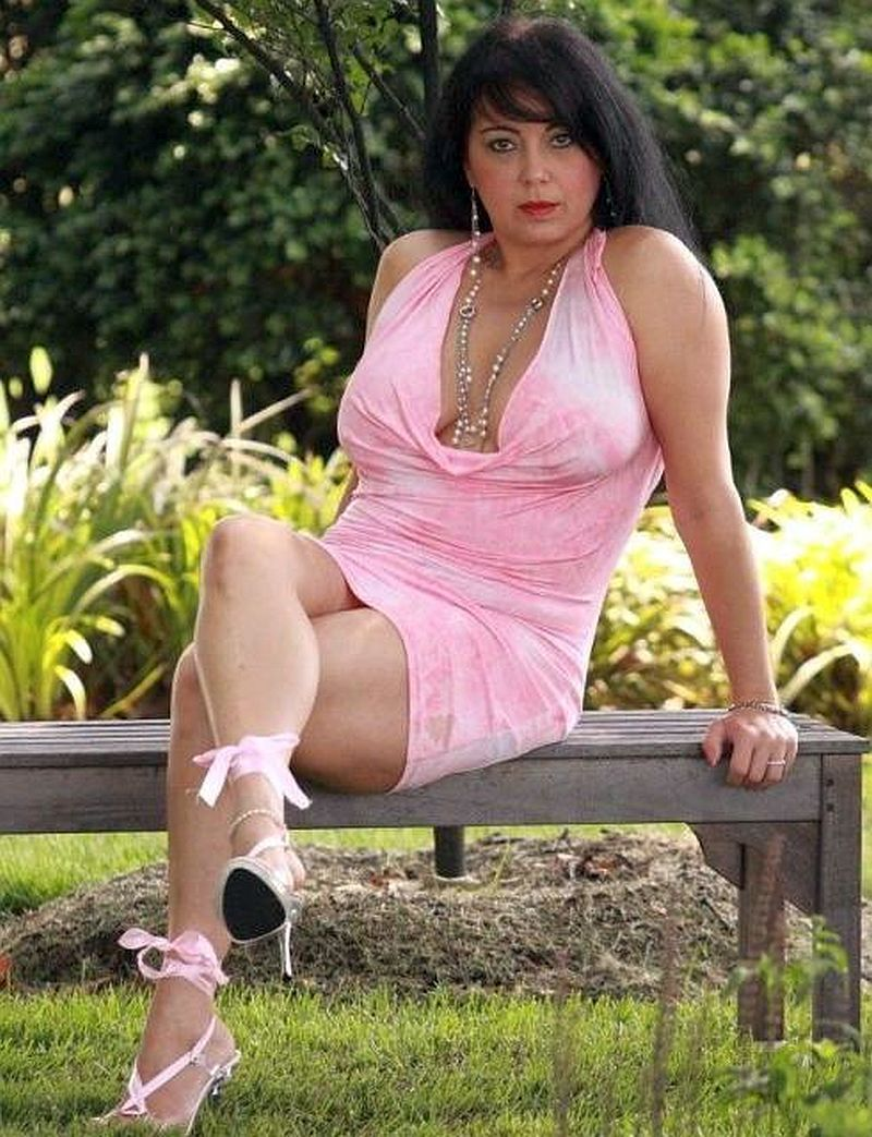 older brunette with big tits sitting on park bench wearing a pink