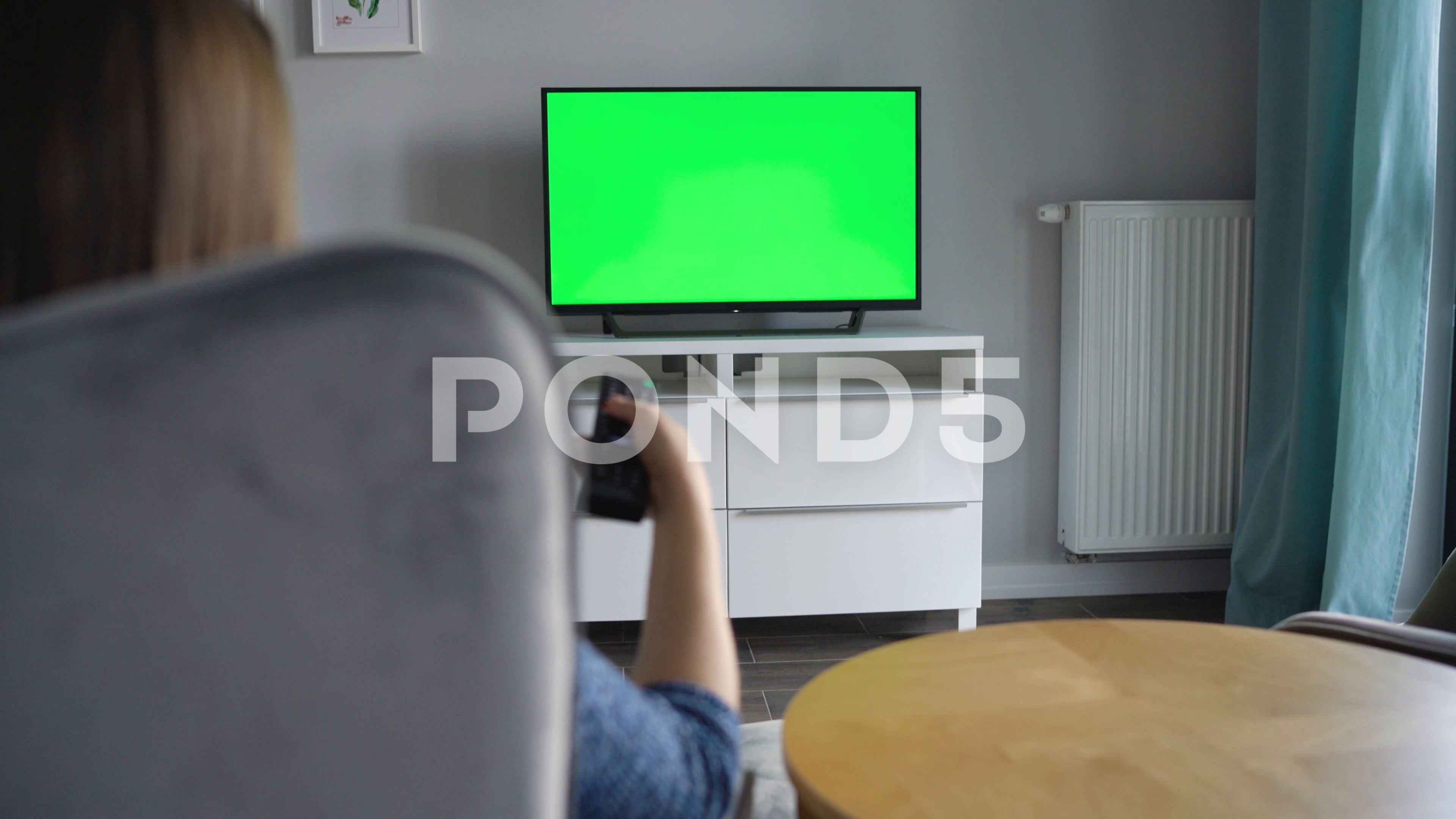 Woman Is Sitting In A Chair Watching Tv With A Green Screen Switching Channels Stock Footage Ad Watching Tv Chair Woman In 2020 Chroma Key Greenscreen Tv Chair