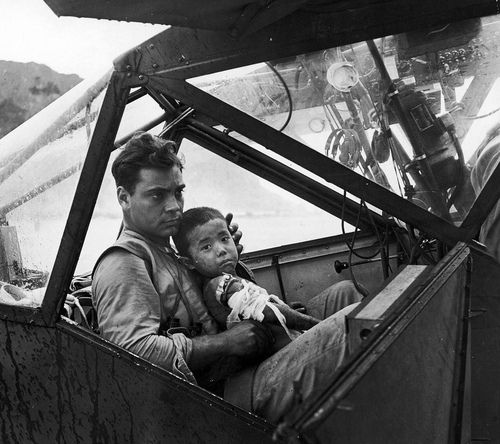 An American soldier holding a wounded Japanese boy inside his airplane while they're waiting for a flight to the nearest field hospital in Saipan by Peter Stackpole. 1944. S)