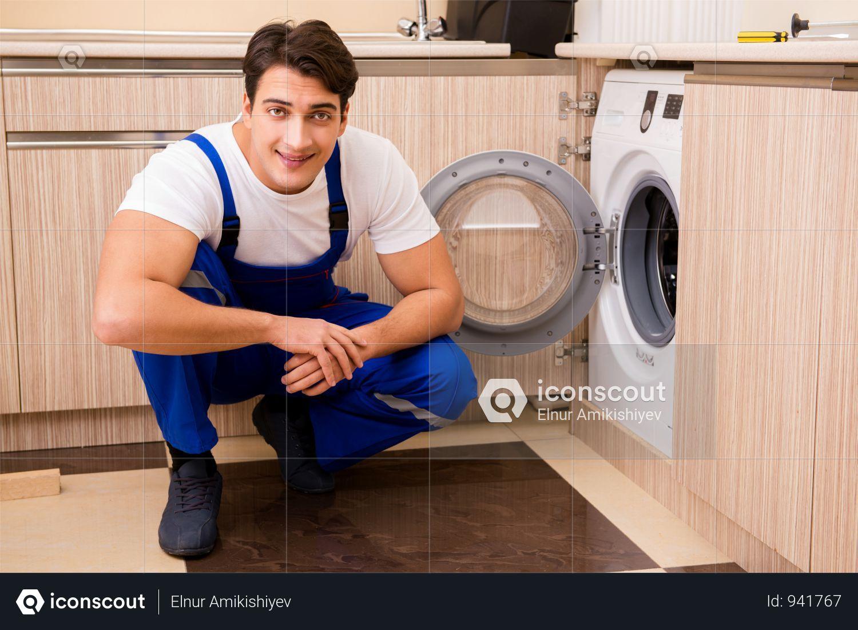 Premium Repairman Repairing Washing Machine At Kitchen Photo