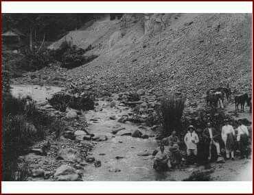 Mannen van Europese en Indo-Europese origine bij hun paarden en inheemse begeleiders aan een rivierbedding te Paloe op Celebes.  1924-1925