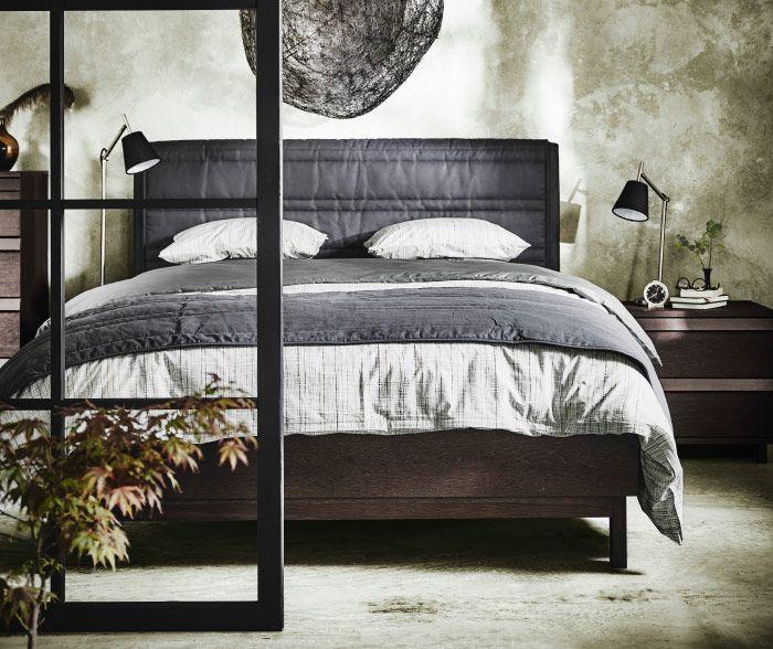 Petsatusta saarniviilusta valmistettu sänky, jossa kankaalla verhoiltu sängynpääty. Sängyssä on beigejä ja harmaita vuodevaatteita.