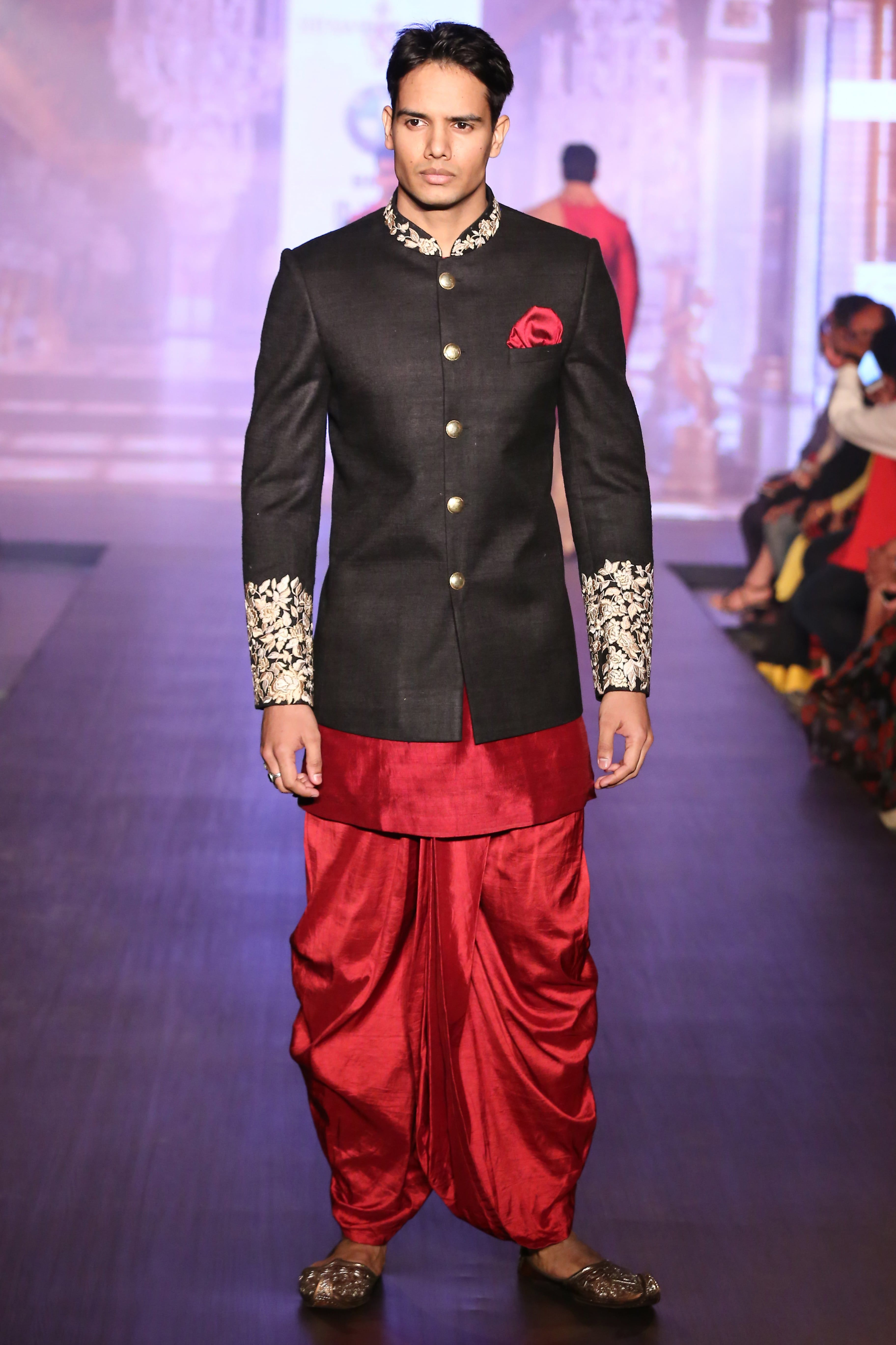 A black jacket with thread embroidery paired with a red dhoti