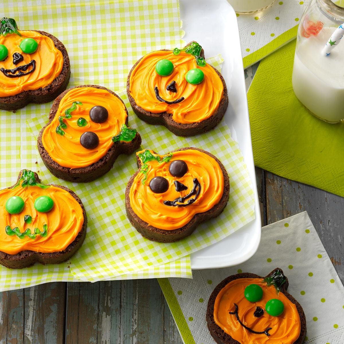 Jack-o'-Lantern Brownies Recipe -Hosting a Halloween party? Use a cookie cutter to easily cut these homemade chocolate brownies into pumpkin shapes, then give them personality with orange, black and green frosting. Our grandchildren think these are great. —Flo Burtnett, Gage, Oklahoma