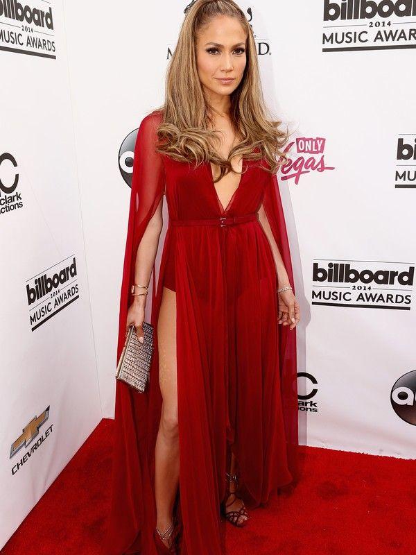 Jennifer Lopez  Cantora apostou em modelito transparente na cor vermelha com fendas bem ousadas. O vestido é da coleção de inverno 2014 da grife Donna Karan. Ela combinou o look com sandálias vermelhas e acessórios metálicos. Agência Getty Images - Getty Image