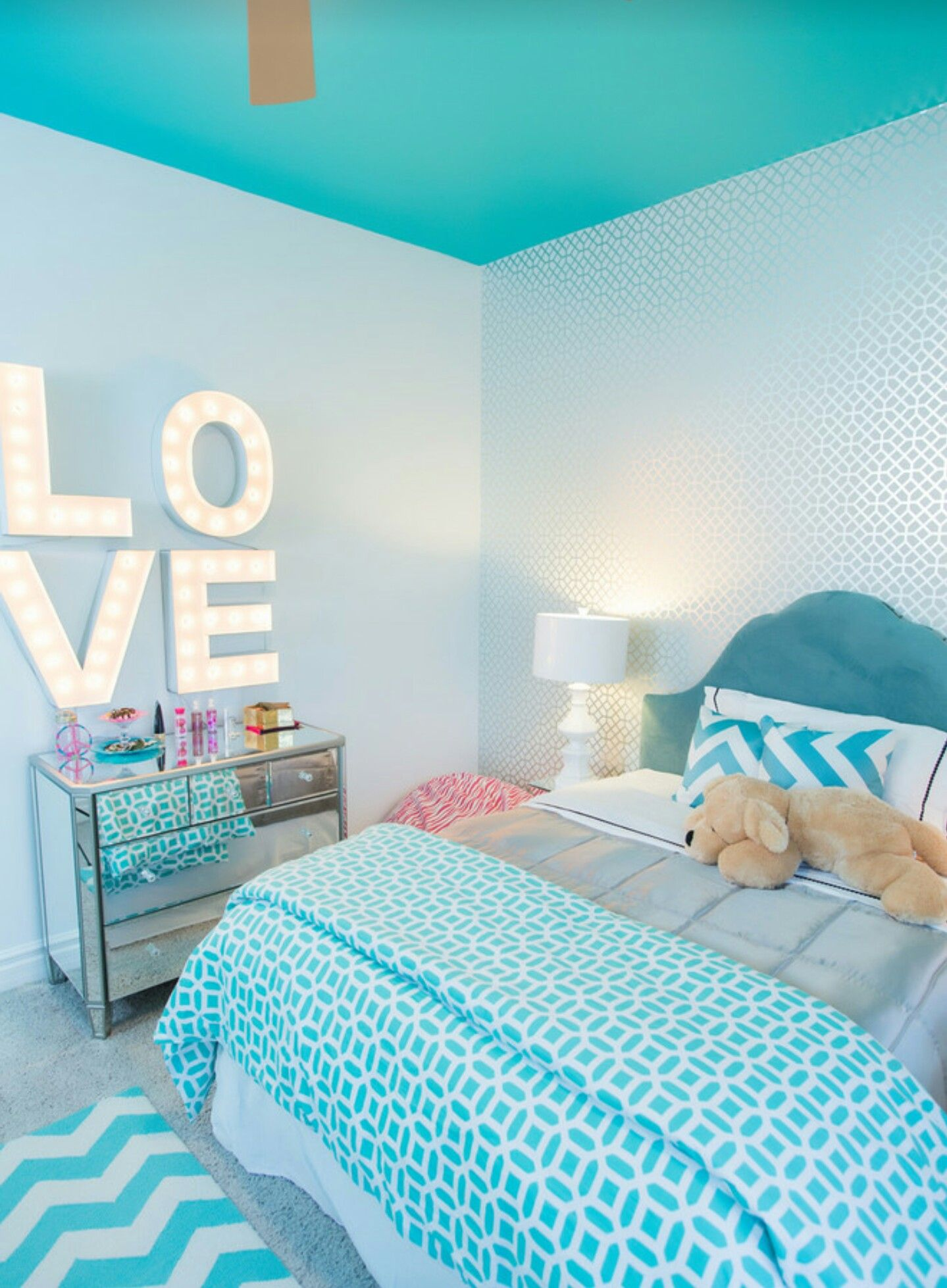 turquoise blue girl's bedroom features a white feather chandelier