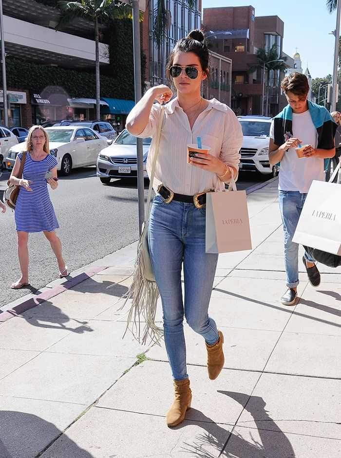 0acc5195673e4 Kendall Jenner wears a white button-down blouse tucked into high-waisted  skinny jeans with a black belt