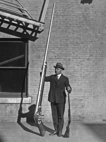 """Chief United States Game Warden George A. Lawyer, with a 10'9"""" punt gun weighing 250 pounds. Used for duck hunting."""