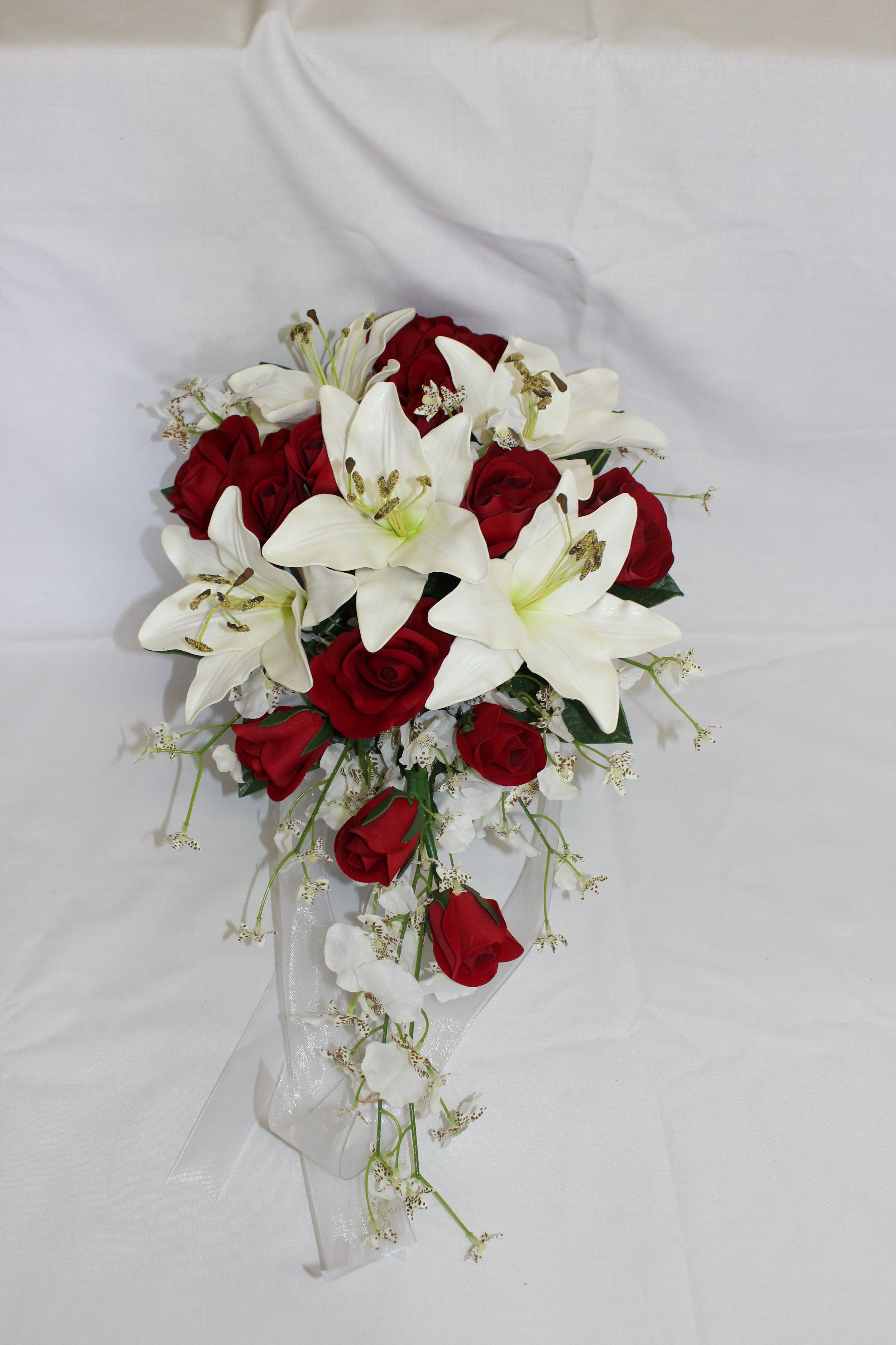 bridal teardrop of white tiger lilies, red rose blooms and buds and ...
